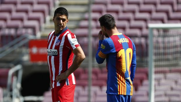 Atletico Madrid's Luis Suarez, left, speaks with Barcelona's Lionel Messi ahead of the Spanish La Liga soccer match between FC Barcelona and Atletico Madrid at the Camp Nou stadium in Barcelona, Spain, Saturday, May 8, 2021. (AP Photo/Joan Monfort)