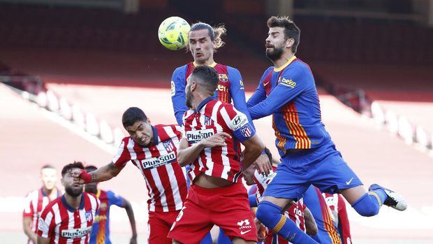 Barcelona's Antoine Griezmann, top left, heads the ball past Atletico Madrid's Koke, center, and Atletico Madrid's Luis Suarez, left, during the Spanish La Liga soccer match between FC Barcelona and Atletico Madrid at the Camp Nou stadium in Barcelona, Spain, Saturday, May 8, 2021. (AP Photo/Joan Monfort)