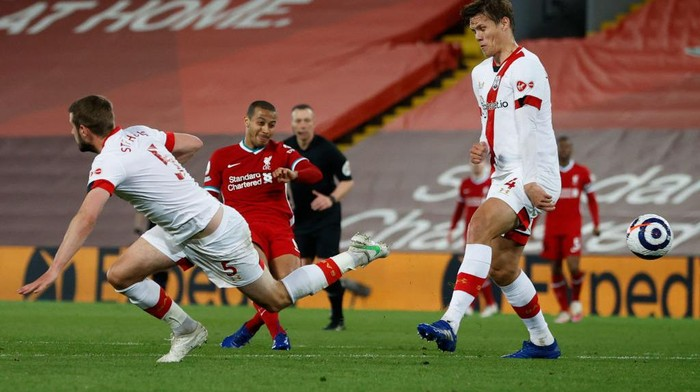 LIVERPOOL, ENGLAND - MAY 08: Thiago of Liverpool scores their sides second goal whilst under pressure from Jack Stephens and Jannik Vestergaard of Southampton during the Premier League match between Liverpool and Southampton at Anfield on May 08, 2021 in Liverpool, England. Sporting stadiums around the UK remain under strict restrictions due to the Coronavirus Pandemic as Government social distancing laws prohibit fans inside venues resulting in games being played behind closed doors. (Photo by Phil Noble - Pool/Getty Images)