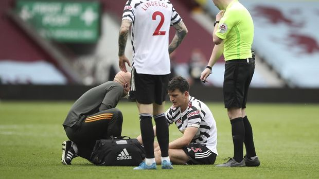 Manchester United's Harry Maguire receives medical treatment during the English Premier League soccer match between Aston Villa and Manchester United at Villa Park in Birmingham, England, Sunday, May 9, 2021. (Nick Potts/Pool via AP)