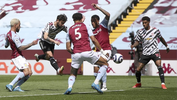 Manchester Uniteds Bruno Fernandes, second left, kicks the ball during the English Premier League soccer match between Aston Villa and Manchester United at Villa Park in Birmingham, England, Sunday, May 9, 2021. (Nick Potts/Pool via AP)