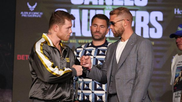 ARLINGTON, TEXAS - MAY 06: Canelo Alvarez and Billy Joe Saunders shake hands with Matchroom Promoter Eddie Hearn looking on during the press conference for Alvarez's WBC and WBA super middleweight titles and Saunders' WBO super middleweight title at Live! by Loews hotel on May 06, 2021 in Arlington, Texas.   Al Bello/Getty Images/AFP (Photo by AL BELLO / GETTY IMAGES NORTH AMERICA / Getty Images via AFP)
