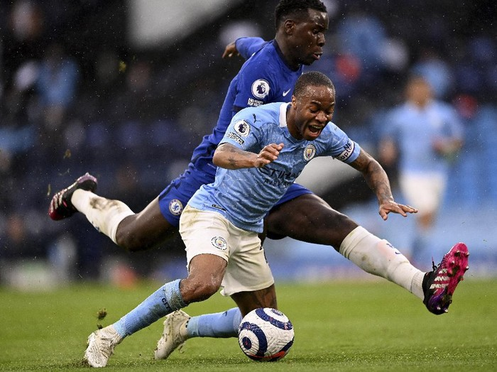 Chelseas Kurt Zouma, rear, and Manchester Citys Raheem Sterling challenge for the ball during the English Premier League soccer match between Manchester City and Chelsea at the Etihad Stadium in Manchester, Saturday, May 8, 2021.(Laurence Griffiths/Pool via AP)
