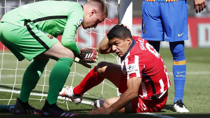 Barcelonas goalkeeper Marc-Andre ter Stegen, left, helps Atletico Madrids Luis Suarez during the Spanish La Liga soccer match between FC Barcelona and Atletico Madrid at the Camp Nou stadium in Barcelona, Spain, Saturday, May 8, 2021. (AP Photo/Joan Monfort)