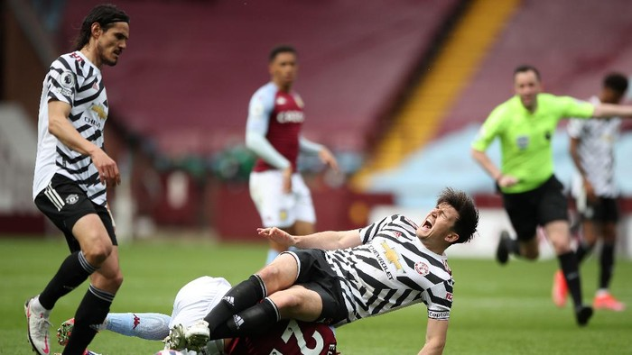 BIRMINGHAM, ENGLAND - MAY 09: Harry Maguire of Manchester United is challenged by Anwar El Ghazi of Aston Villa during the Premier League match between Aston Villa and Manchester United at Villa Park on May 09, 2021 in Birmingham, England. Sporting stadiums around the UK remain under strict restrictions due to the Coronavirus Pandemic as Government social distancing laws prohibit fans inside venues resulting in games being played behind closed doors. (Photo by Nick Potts - Pool/Getty Images)