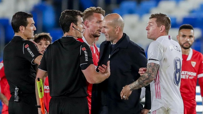Real Madrids head coach Zinedine Zidane talks with the referre at the end of the Spanish La Liga soccer match between Real Madrid and Sevilla at the Alfredo di Stefano stadium in Madrid, Spain, Sunday, May 9, 2021. (AP Photo/Manu Fernandez)