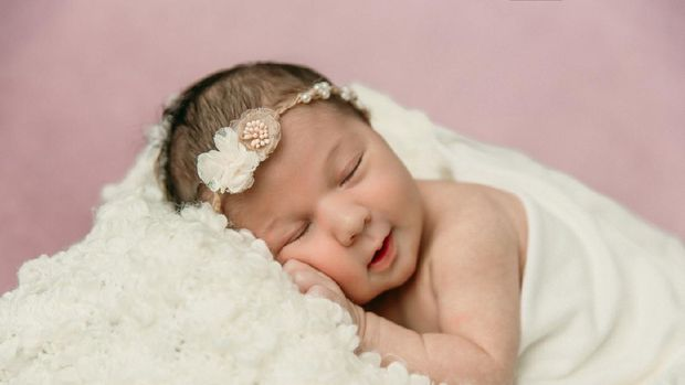 Sleeping newborn baby girl laying on a cream colored blanket on a pink purple backdrop with a headband in her hair and a slight smile