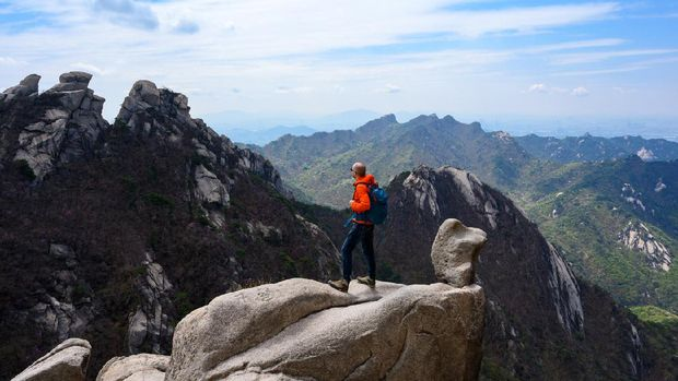 Backpacker is enjoying a weekend in nature hiking at Bukhansan National Park near Seoul, Korea.