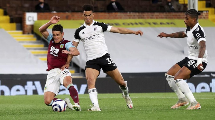 LONDON, ENGLAND - MAY 10: Ashley Westwood of Burnley scores their teams first goal under pressure from Antonee Robinson of Fulham during the Premier League match between Fulham and Burnley at Craven Cottage on May 10, 2021 in London, England. Sporting stadiums around the UK remain under strict restrictions due to the Coronavirus Pandemic as Government social distancing laws prohibit fans inside venues resulting in games being played behind closed doors. (Photo by Clive Rose/Getty Images)