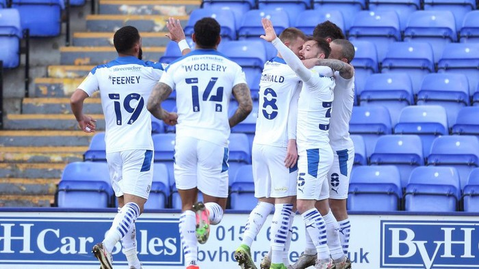 BIRKENHEAD, ENGLAND - APRIL 05: Paul Lewis of Tranmere Rovers celebrates with Liam Feeney, Calum MacDonald and Danny Lloyd after scoring their sides first goal during the Sky Bet League Two match between Tranmere Rovers and Cambridge United at Prenton Park on April 05, 2021 in Birkenhead, England. Sporting stadiums around the UK remain under strict restrictions due to the Coronavirus Pandemic as Government social distancing laws prohibit fans inside venues resulting in games being played behind closed doors. (Photo by Lewis Storey/Getty Images)