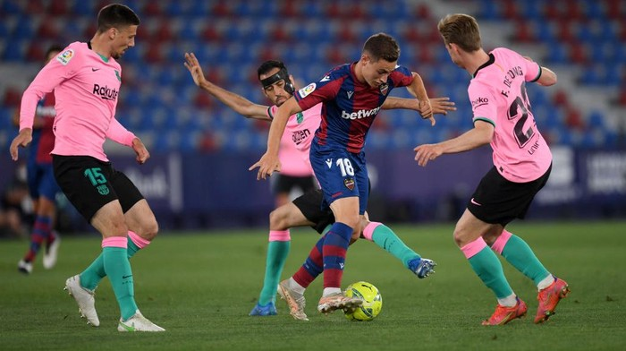 VALENCIA, SPAIN - MAY 11: Frutos of Levante UD is tackled by Clement Lenglet, Sergio Busquets and Frenkie de Jong of Barcelona during the La Liga Santander match between Levante UD and FC Barcelona at Ciutat de Valencia Stadium on May 11, 2021 in Valencia, Spain. Sporting stadiums around Spain remain under strict restrictions due to the Coronavirus Pandemic as Government social distancing laws prohibit fans inside venues resulting in games being played behind closed doors. (Photo by Alex Caparros/Getty Images)