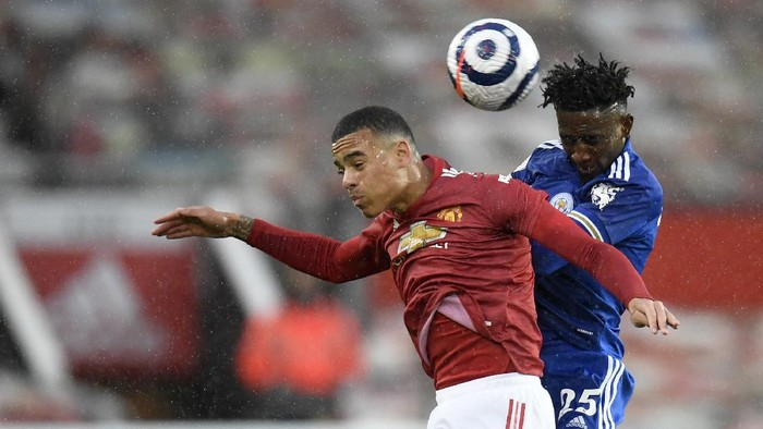 Manchester Uniteds Mason Greenwood jumps for the ball with Leicesters Wilfred Ndidi during the English Premier League soccer match between Manchester United and Leicester City, at the Old Trafford stadium in Manchester, England, Tuesday, May 11, 2021. (Peter Powell/Pool via AP)