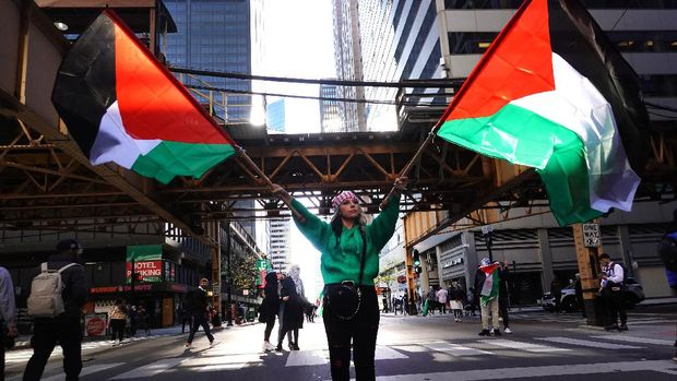 CHICAGO, ILLINOIS - MAY 12: A demonstrator waves Palestinian flags as she leads thousands marching through downtown toward the Israeli consulate to protest Israeli airstrikes in the Gaza Strip on May 12, 2021 in Chicago, Illinois. The death toll in Gaza continues to rise as the region is seeing the worst outbreak of violence since the 2014 Gaza war.   Scott Olson/Getty Images/AFP (Photo by SCOTT OLSON / GETTY IMAGES NORTH AMERICA / Getty Images via AFP)