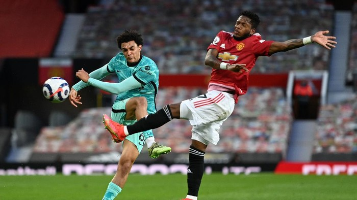 MANCHESTER, ENGLAND - MAY 13: Trent Alexander-Arnold of Liverpool is challenged by Fred of Manchester United during the Premier League match between Manchester United and Liverpool at Old Trafford on May 13, 2021 in Manchester, England. Sporting stadiums around the UK remain under strict restrictions due to the Coronavirus Pandemic as Government social distancing laws prohibit fans inside venues resulting in games being played behind closed doors. (Photo by Michael Regan/Getty Images)