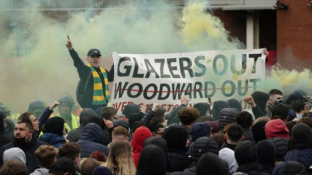 Manchester United fans let off flares and hold a banner as they protest against the Glazer family, the American owners of Manchester United, before their English Premier League soccer match against Liverpool at Old Trafford stadium in Manchester, England, Thursday, May 13, 2021. (AP Photo/Jon Super)