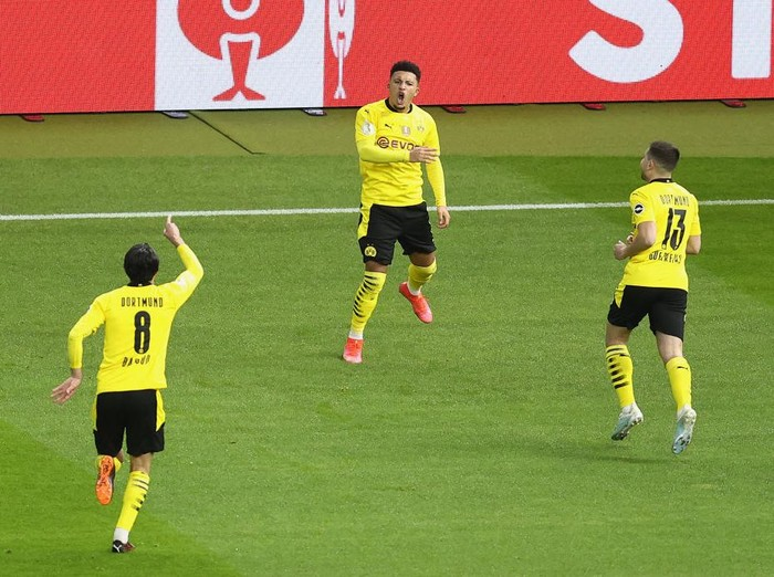 BERLIN, GERMANY - MAY 13: Jadon Sancho (C) of Borussia Dortmund celebrates his teams first goal with teammates Mahmoud Dahoud (L) and Raphael Guerreiro during the DFB Cup final match between RB Leipzig and Borussia Dortmund at Olympic Stadium on May 13, 2021 in Berlin, Germany. Sporting stadiums around Germany remain under strict restrictions due to the Coronavirus Pandemic as Government social distancing laws prohibit fans inside venues resulting in games being played behind closed doors. (Photo by Maja Hitij/Getty Images)