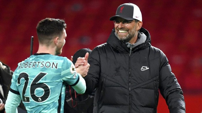Liverpools manager Jurgen Klopp, right, shakes hands with Liverpools Andrew Robertson at the end of the English Premier League soccer match between Manchester United and Liverpool, at the Old Trafford stadium in Manchester, England, Thursday, May 13, 2021. (Michael Regan/Pool via AP)