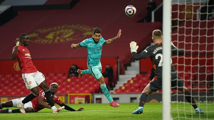 MANCHESTER, ENGLAND - MAY 13: Roberto Firmino of Liverpool scores their sides second goal past Dean Henderson of Manchester United during the Premier League match between Manchester United and Liverpool at Old Trafford on May 13, 2021 in Manchester, England. Sporting stadiums around the UK remain under strict restrictions due to the Coronavirus Pandemic as Government social distancing laws prohibit fans inside venues resulting in games being played behind closed doors. (Photo by Dave Thompson - Pool/Getty Images)