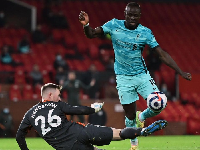 MANCHESTER, ENGLAND - MAY 13: Sadio Mane of Liverpool is challenged by Dean Henderson of Manchester United during the Premier League match between Manchester United and Liverpool at Old Trafford on May 13, 2021 in Manchester, England. Sporting stadiums around the UK remain under strict restrictions due to the Coronavirus Pandemic as Government social distancing laws prohibit fans inside venues resulting in games being played behind closed doors. (Photo by Peter Powell - Pool/Getty Images)