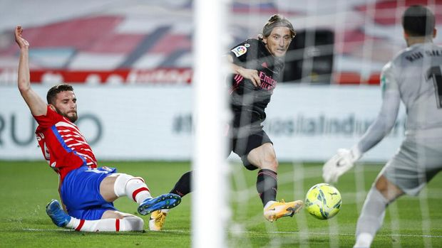 Real Madrid's Luka Modric, center, scores the opening goal during the Spanish La Liga soccer match between Granada and Real Madrid at Los Carmenes stadium in Granada, Spain, Thursday, May 13, 2021. (AP Photo/Fermin Rodriguez)
