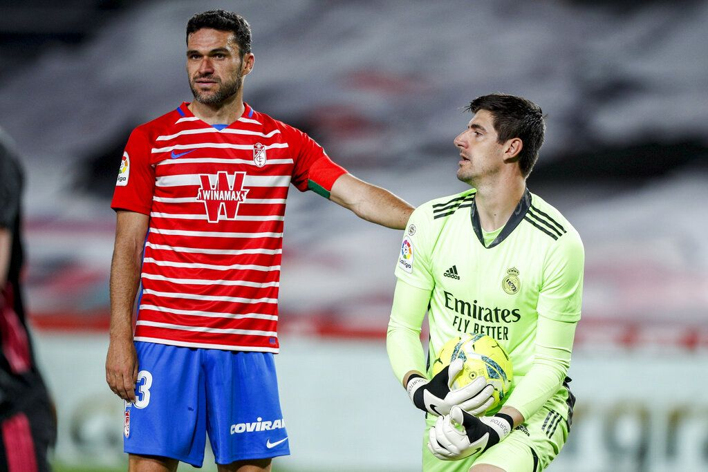 Granada's Jorge Molina, left, stands next to Real Madrid's goalkeeper Thibaut Courtois during the Spanish La Liga soccer match between Granada and Real Madrid at Los Carmenes stadium in Granada, Spain, Thursday, May 13, 2021. (AP Photo/Fermin Rodriguez)