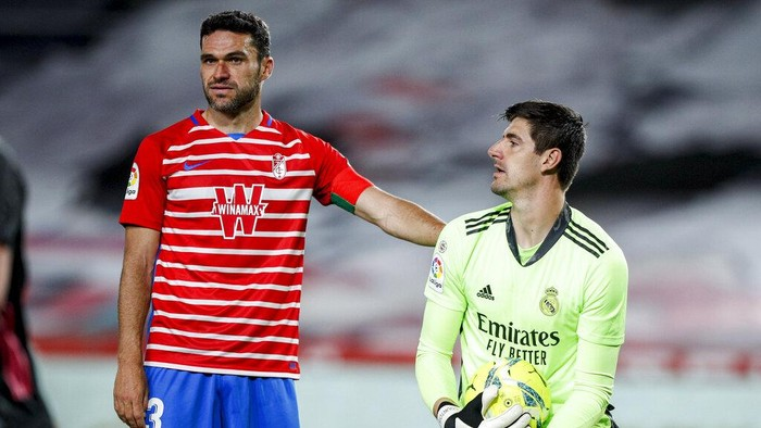 Granadas Jorge Molina, left, stands next to Real Madrids goalkeeper Thibaut Courtois during the Spanish La Liga soccer match between Granada and Real Madrid at Los Carmenes stadium in Granada, Spain, Thursday, May 13, 2021. (AP Photo/Fermin Rodriguez)