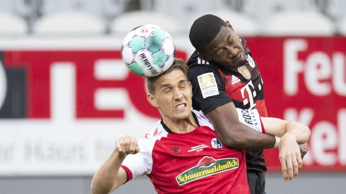 Freiburgs Nils Petersen, left, and Bayerns David Alaba challenge for the ball during the German Bundesliga soccer match between SC Freiburg and FC Bayern Munich in Freiburg, Germany, Saturday, May 15, 2021. (Tom Weller/dpa via AP)