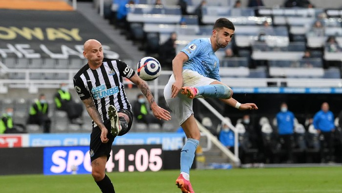 NEWCASTLE UPON TYNE, ENGLAND - MAY 14: Ferran Torres of Manchester City scores their sides second goal whilst under pressure from Jonjo Shelvey of Newcastle United during the Premier League match between Newcastle United and Manchester City at St. James Park on May 14, 2021 in Newcastle upon Tyne, England. Sporting stadiums around the UK remain under strict restrictions due to the Coronavirus Pandemic as Government social distancing laws prohibit fans inside venues resulting in games being played behind closed doors.  (Photo by Stu Forster/Getty Images)
