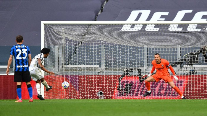 TURIN, ITALY - MAY 15: Juan Cuadrado of Juventus scores their sides third goal from the penalty spot past Samir Handanovic of FC Internazionale during the Serie A match between Juventus and FC Internazionale at Allianz Stadium on May 15, 2021 in Turin, Italy. Sporting stadiums around Italy remain under strict restrictions due to the Coronavirus Pandemic as Government social distancing laws prohibit fans inside venues resulting in games being played behind closed doors.  (Photo by Valerio Pennicino/Getty Images)