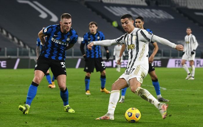 TURIN, ITALY - FEBRUARY 09: Cristiano Ronaldo of Juventus controls the ball against Milan Skriniar of FC Internazionale during the Coppa Italia semi-final match between Juventus and FC Internazionale at Allianz Stadium on February 9, 2021 in Turin, Italy. Sporting stadiums around Italy remain under strict restrictions due to the Coronavirus Pandemic as Government social distancing laws prohibit fans inside venues resulting in games being played behind closed doors. (Photo by Chris Ricco/Getty Images)