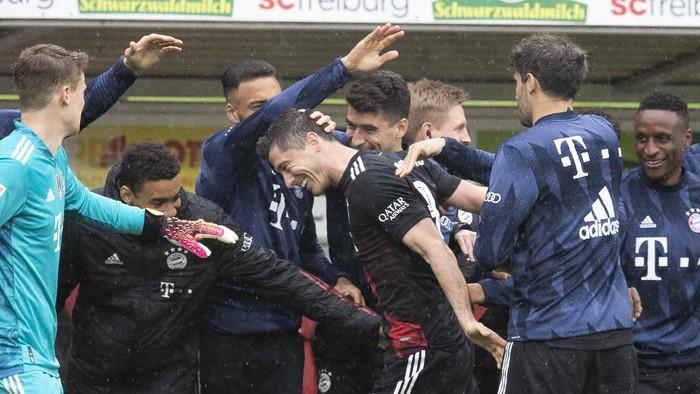 Bayerns Robert Lewandowski, center, celebrates with team mates after scoring during the German Bundesliga soccer match between SC Freiburg and FC Bayern Munich in Freiburg, Germany, Saturday, May 15, 2021. (Tom Weller/dpa via AP)