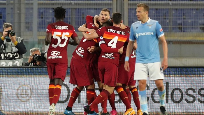 ROME, ITALY - MAY 15: Edin Dzeko of A.S Roma celebrates with team mates after scoring their sides first goal during the Serie A match between AS Roma  and SS Lazio at Stadio Olimpico on May 15, 2021 in Rome, Italy. Sporting stadiums around Italy remain under strict restrictions due to the Coronavirus Pandemic as Government social distancing laws prohibit fans inside venues resulting in games being played behind closed doors. (Photo by Paolo Bruno/Getty Images)