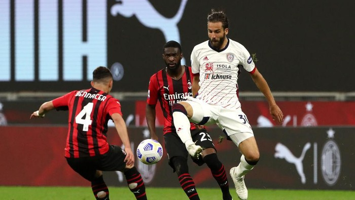 MILAN, ITALY - MAY 16: Leonardo Pavoletti of Cagliari Calcio controls the ball whilst under pressure from Ismael Bennacer and Fikayo Tomori of AC Milan during the Serie A match between AC Milan  and Cagliari Calcio at Stadio Giuseppe Meazza on May 16, 2021 in Milan, Italy. Sporting stadiums around Italy remain under strict restrictions due to the Coronavirus Pandemic as Government social distancing laws prohibit fans inside venues resulting in games being played behind closed doors. (Photo by Marco Luzzani/Getty Images)