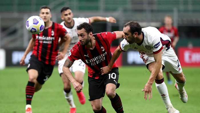 MILAN, ITALY - MAY 16: Hakan Calhanoglu of AC Milan battles for possession with Diego Godin of Cagliari Calcio during the Serie A match between AC Milan  and Cagliari Calcio at Stadio Giuseppe Meazza on May 16, 2021 in Milan, Italy. Sporting stadiums around Italy remain under strict restrictions due to the Coronavirus Pandemic as Government social distancing laws prohibit fans inside venues resulting in games being played behind closed doors. (Photo by Marco Luzzani/Getty Images)