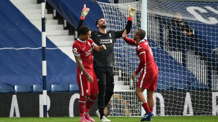 WEST BROMWICH, ENGLAND - MAY 16: Alisson of Liverpool celebrates with team mates (L - R) Roberto Firmino and Thiago after scoring their sides second goal during the Premier League match between West Bromwich Albion and Liverpool at The Hawthorns on May 16, 2021 in West Bromwich, England. Sporting stadiums around the UK remain under strict restrictions due to the Coronavirus Pandemic as Government social distancing laws prohibit fans inside venues resulting in games being played behind closed doors. (Photo by Rui Vieira - Pool/Getty Images)