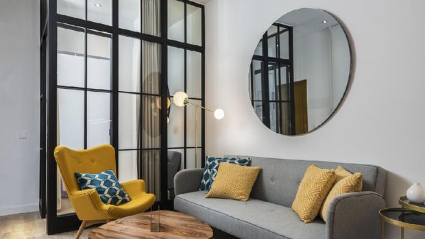 Colorful and cozy living room with a designer armchair and sofa along with a round decorative mirror and glass wall.