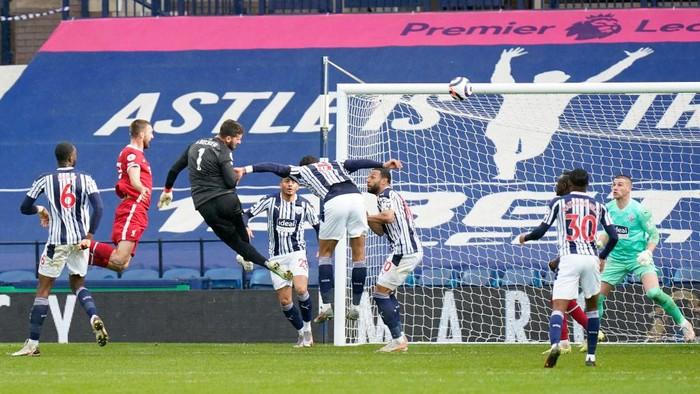 WEST BROMWICH, ENGLAND - MAY 16: Alisson of Liverpool scores their sides second goal past Sam Johnstone of West Bromwich Albion during the Premier League match between West Bromwich Albion and Liverpool at The Hawthorns on May 16, 2021 in West Bromwich, England. Sporting stadiums around the UK remain under strict restrictions due to the Coronavirus Pandemic as Government social distancing laws prohibit fans inside venues resulting in games being played behind closed doors. (Photo by Tim Keeton - Pool/Getty Images)