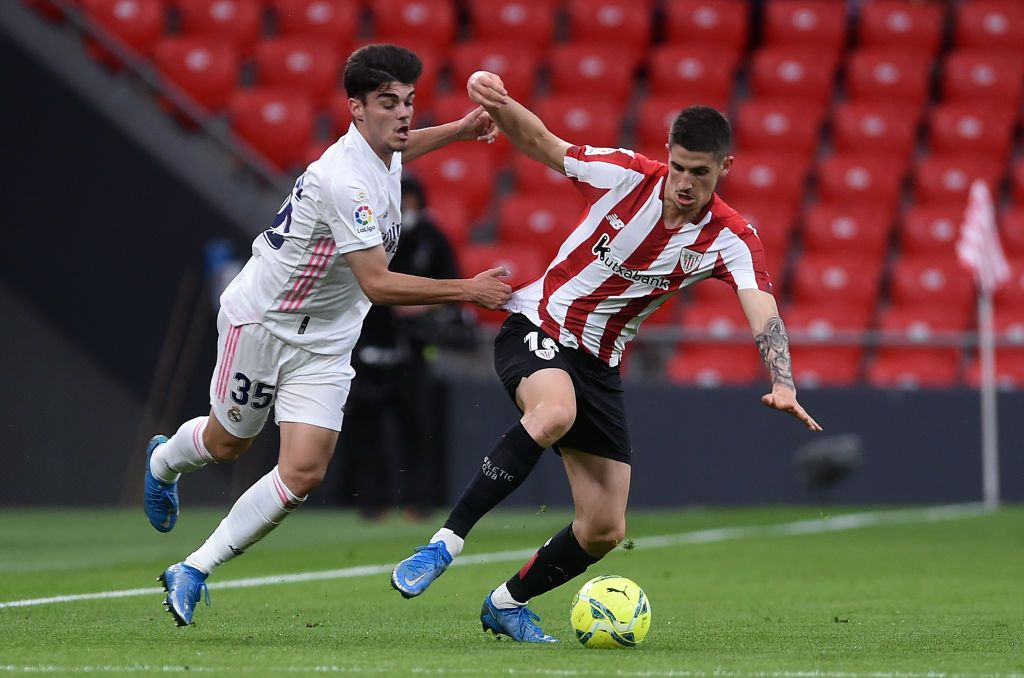 BILBAO, SPAIN - MAY 16: Oihan Sancet of Athletic Club is challenged by Miguel Gutierrez of Real Madrid during the La Liga Santander match between Athletic Club and Real Madrid at Estadio de San Mames on May 16, 2021 in Bilbao, Spain. Sporting stadiums around Spain remain under strict restrictions due to the Coronavirus Pandemic as Government social distancing laws prohibit fans inside venues resulting in games being played behind closed doors.  (Photo by Juan Manuel Serrano Arce/Getty Images)