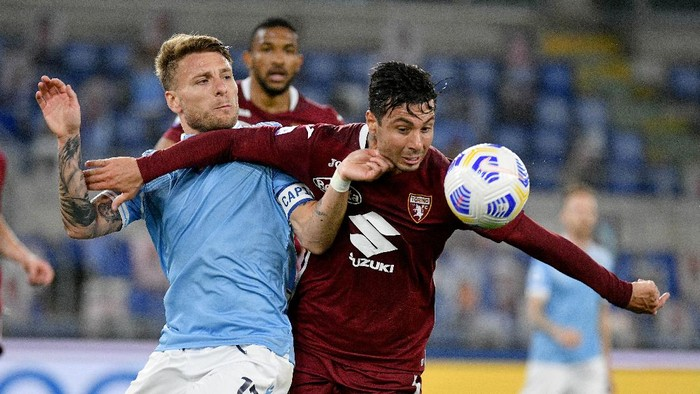 ROME, ITALY - MAY 18: Ciro Immobile of SS Lazio compete for the ball with Armando Izzo of Torino FC during the Serie A match between SS Lazio  and Torino FC at Stadio Olimpico on May 18, 2021 in Rome, Italy. (Photo by Marco Rosi - SS Lazio/Getty Images)