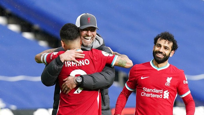 Liverpools manager Jurgen Klopp, center, celebrates with Liverpools Roberto Firmino, front, and Liverpools Mohamed Salah at the end of the English Premier League soccer match between West Bromwich Albion and Liverpool at the Hawthorns stadium in West Bromwich, England, Sunday, May 16, 2021. (Tim Keeton/Pool via AP)