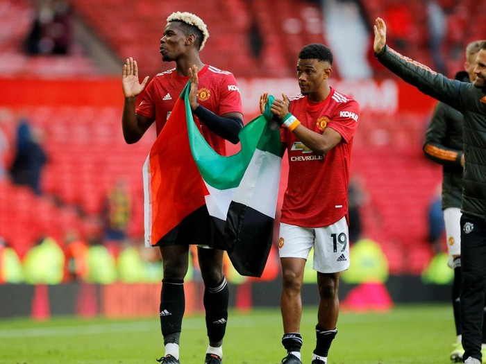 MANCHESTER, ENGLAND - MAY 18: Paul Pogba and Amad Diallo of Manchester United applaud the fans whilst holding a Palestine flag after the Premier League match between Manchester United and Fulham at Old Trafford on May 18, 2021 in Manchester, England. A limited number of fans will be allowed into Premier League stadiums as Coronavirus restrictions begin to ease in the UK following the COVID-19 pandemic. (Photo by Phil Noble - Pool/Getty Images)