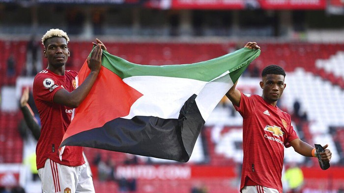 Manchester Uniteds Paul Pogba, left, and Manchester Uniteds Amad Diallo hold up the flag of Palestine after the English Premier League soccer match between Manchester United and Fulham at Old Trafford stadium in Manchester, England, Tuesday, May 18, 2021. (AP Photo/Laurence Griffiths, Pool)