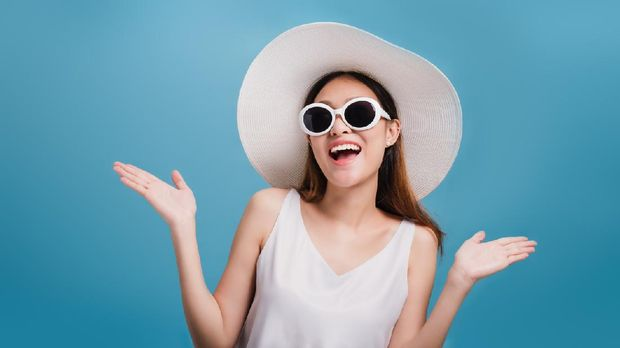 Asian smiling beautiful women blogger wear a wide hat and wear sunglasses isolated in blue color background with copy space.Concept of Travel business with Promotion and Sale.