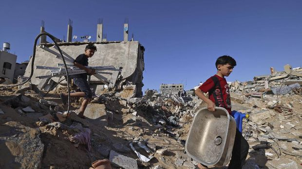 Palestinian children carry household items they recovered from the rubble of a building, destroyed by Israeli strikes, in Beit Hanun in the northern Gaza Strip on May 21, 2021. - A ceasefire in the conflict between Israel and Palestinian militants in the Gaza Strip, controlled by Islamist group Hamas, came into effect after 11 days of airstrikes and rocket fire. (Photo by Emmanuel DUNAND / AFP)