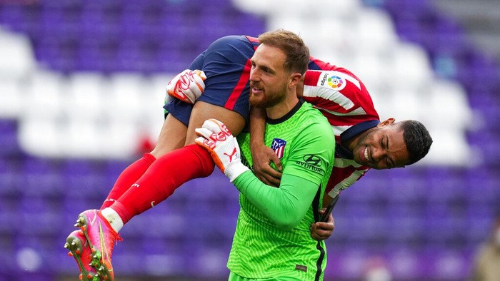 Atletico Madrids goalkeeper Jan Oblak celebrates with teammate Renan Lodi, top, at the end of the Spanish La Liga soccer match between Atletico Madrid and Valladolid at the Jose Zorrilla stadium in Valladolid, Spain, Saturday, May 22, 2021. Atletico won 2-1 and clinches its 11th Spanish La Liga title. (AP Photo/Manu Fernandez)