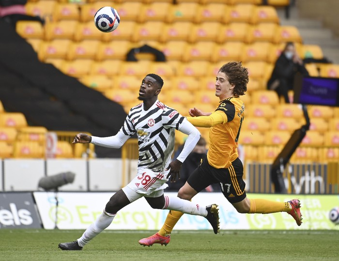 Wolverhampton Wanderers Fabio Silva, right, and Manchester Uniteds Bruno Fernandes challenge for the ball during the English Premier League soccer match between Wolverhampton Wanderers and Manchester United at the Molineux Stadium in Wolverhampton, England, Sunday, May 23, 2021. (Andy Rain/Pool via AP)