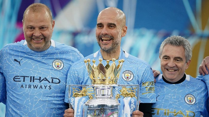 MANCHESTER, ENGLAND - MAY 23: Rodolfo Borrell, Assistant Coach of Manchester City, Pep Guardiola, Manager of Manchester City, and Juanma Lillo, Assistant Manager of Manchester City celebrates with the Premier League Trophy as Manchester City are presented with the Trophy as they win the league following the Premier League match between Manchester City and Everton at Etihad Stadium on May 23, 2021 in Manchester, England. A limited number of fans will be allowed into Premier League stadiums as Coronavirus restrictions begin to ease in the UK. (Photo by Dave Thompson - Pool/Getty Images)