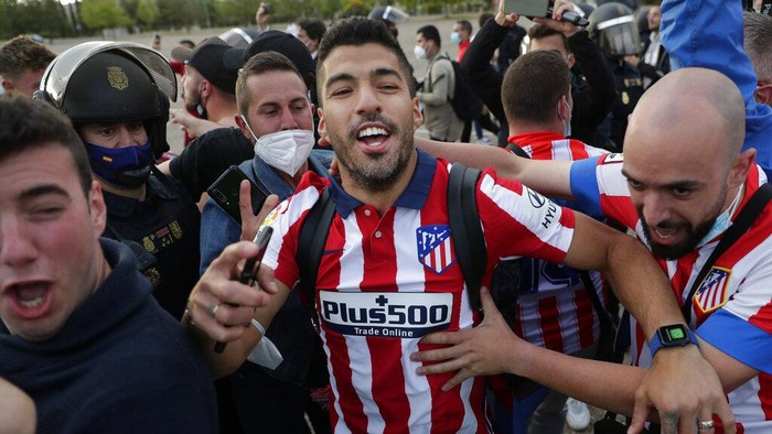 Atletico Madrids Luis Suarez celebrates with supporters after the Spanish La Liga soccer match between Atletico Madrid and Valladolid at the Jose Zorrilla stadium in Valladolid, Spain, Saturday, May 22, 2021. Atletico won 2-1 and clinches its 11th Spanish La Liga title. (AP Photo/Manu Fernandez)