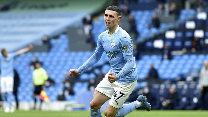 Manchester Citys Phil Foden celebrates scoring his sides third goal during the English Premier League soccer match between Manchester City and Everton at the Etihad stadium in Manchester, Sunday, May 23, 2021.(Peter Powel/Pool via AP)