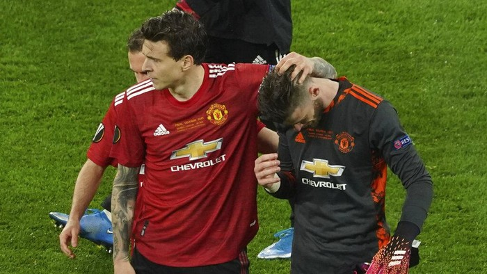 Manchester Uniteds goalkeeper David de Gea, right, its consoled by Victor Lindelof after de Gea missed a penalty giving victory to Villarreal during the Europa League final soccer match between Manchester United and Villarreal in Gdansk, Poland, Wednesday May 26, 2021. (Aleksandra Szmigiel, Pool via AP)